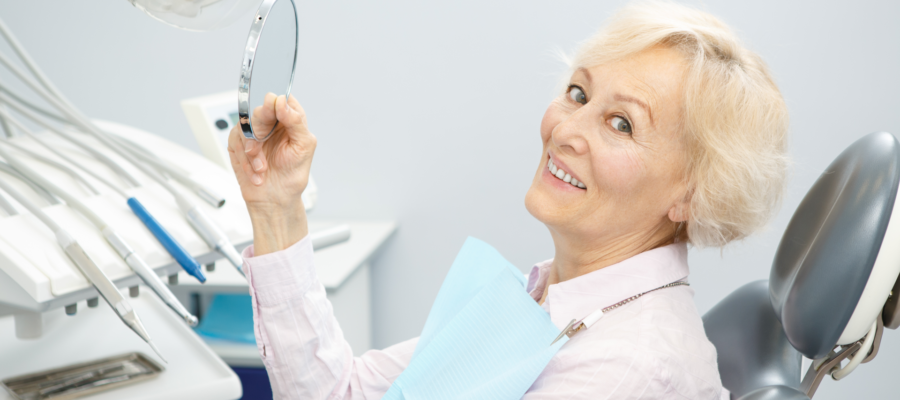 Senior female patient smiling to the camera holding a mirror sitting in a dental chair